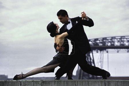 Photo pour Couple latine danse Tango dans la rue, l'homme et une femme dans la danse plus romantique : tango. Danseurs de Tango en action - image libre de droit