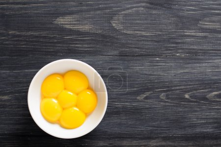 Egg yolks in a bowl on a wooden table...