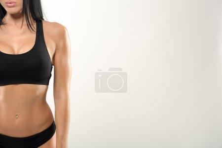 Beautiful fitness model on a gray