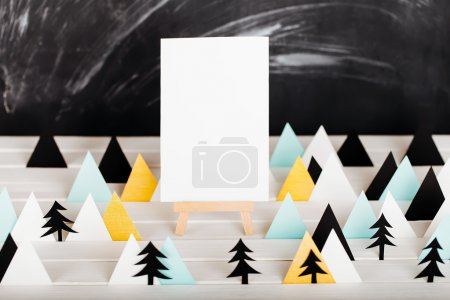 Small easel with sheet of paper and stylized paper tree and mountains