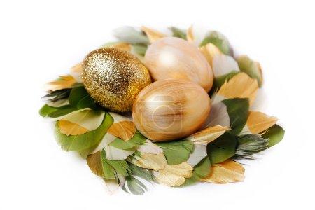 Photo pour Oeufs de Pâques d'or dans une couronne de plumes vertes et or bricolage - image libre de droit