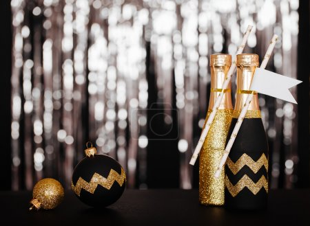 New Years Eve Decorating Ideas for your home or party. Golden champagne and Christmas ball with Chevron pattern on the shiny background