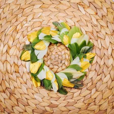 Wreath of feathers woven straw background