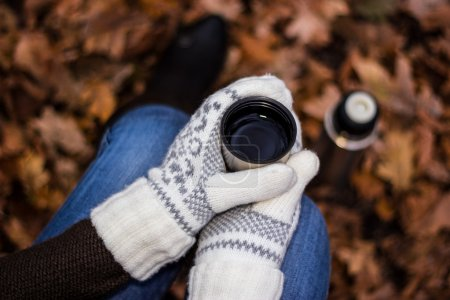 Photo for Sitting woman in white mittens, jeans and boots drink tea or coffee from thermos in autumn park or forest. Theme of hiking, leisure, vacation - Royalty Free Image