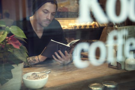 Portrait of handsome white hipster man read a book in cafe near window