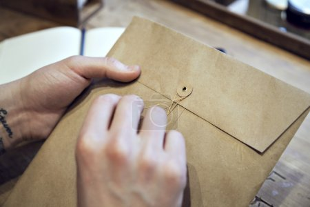 Close-up view of male hands holding brown envelope with coffee at the wooden desk
