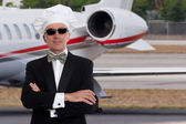 Elegant chef posing in front of a private jet