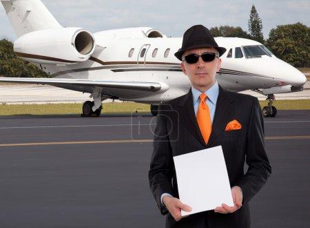 Photo pour Homme d'affaires à côté d'un jet privé détenant une pile de papiers - image libre de droit