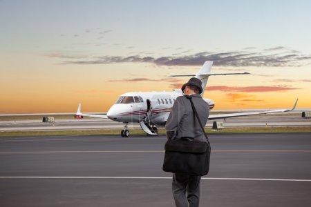 Photo pour Homme d'affaires marchant vers un jet privé - image libre de droit