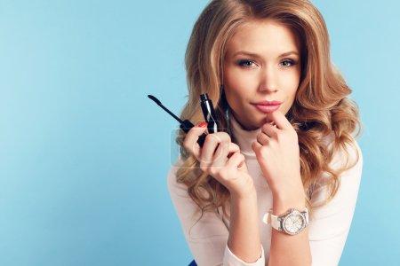 beautiful young woman holding mascara