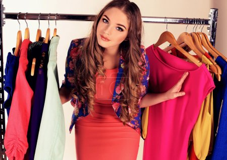 Photo for Fashion studio photo of beautiful young girl with dark curly hair in elegant dress, posing in wardrobe room, choosing a dress - Royalty Free Image