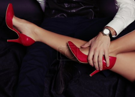 Photo for Fashion photo of impassioned couple.office love story. woman's legs in red elegant shoes in hands of elegant business like man - Royalty Free Image