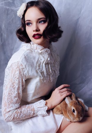 Photo for Fashion studio photo of beautiful young girl with dark short hair wears retro clothes, holding a little rabbit - Royalty Free Image