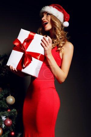 Sexy Blonde Santa holding Christmas gift