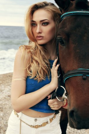 Beautiful woman posing with black horse