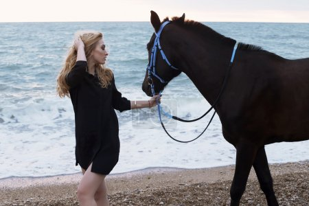 Beautiful woman posing with black horse