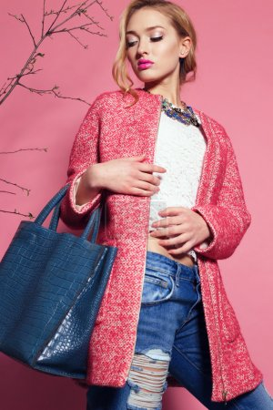Photo for Fashion studio photo of gorgeous young woman with blond curly hair wears elegant pink coat, blouse and jeans, holding a big bag in hands - Royalty Free Image