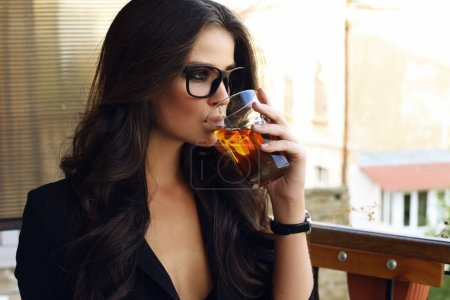 Photo for Fashion photo of beautiful sexy business woman with dark curly hair wearing black jacket, watch and  glasses, sitting at cafe and drinking tea - Royalty Free Image