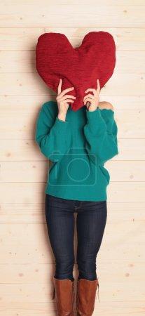 Photo pour Photo d'intérieur de mode de la femme en vêtements décontractés, tenant grand coeur rouge dans les mains, symbole de l'amour - image libre de droit