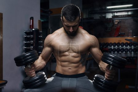 Muscular topless man sitting with dumbbells
