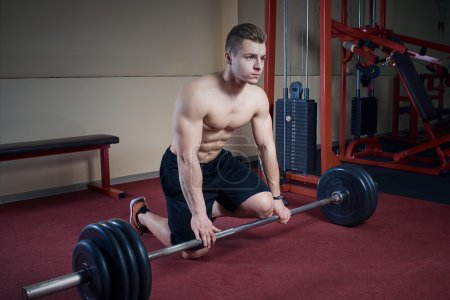 Muscular topless man sitting with barbell