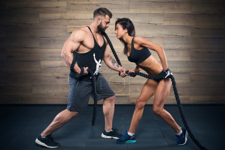 Muscular man with beard and beauty girl pulling a rope