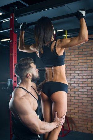 Muscular man with beard coaching beauty girl