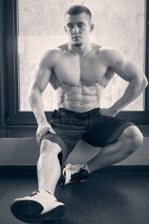 Muscular man sitting on windowsill in gym