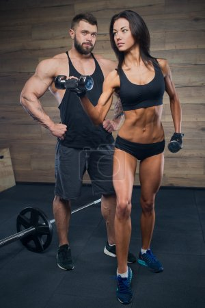 Muscular man with tattoos and beard and beauty girl posing