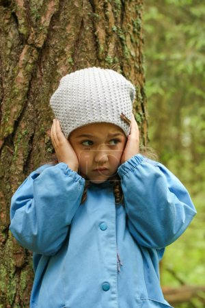 Photo for Little girl in a blue cloak, lost in the woods. - Royalty Free Image