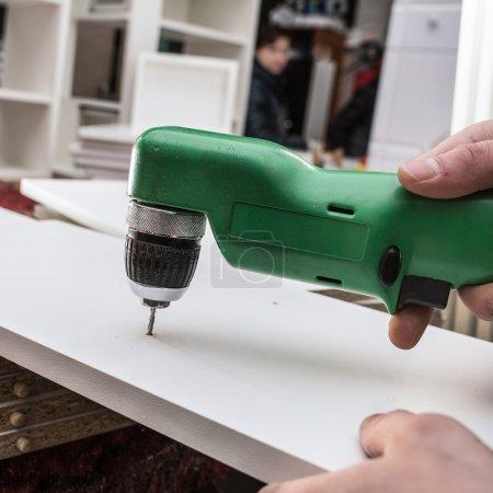Tischler bohrt Loch in die Bauteile einer weißen Küche