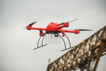 Red industrial drone flies over metal structures industrial faci