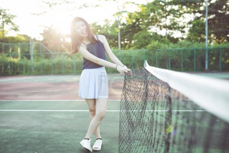 beautiful asian girl on tennis court after playing tennis