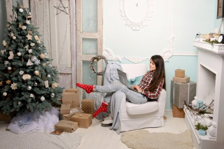 a young woman in a Christmas interior, looking at laptop, guide presents, works