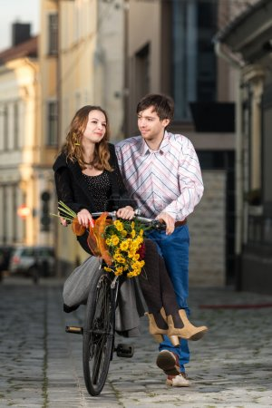 Young man pushing his girlfriend on the bicycle