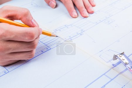 Man's hand with a compass. Mechanical engineer at work. Technical drawings. Pencil, compass, calculator and hand man. Paper with technical drawings and diagrams.