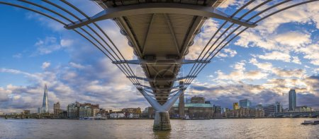 Panoramic skyline taken under the Millennium Bridge at sunset with beautiful sky and clouds - London, UK