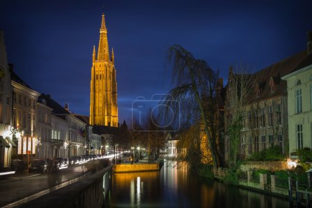 Bruges night scene with canal and church at blue hour, Belgium