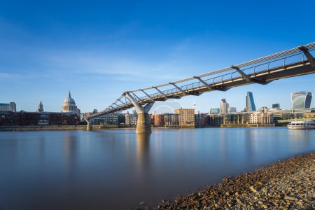 St Paul's Cathedral and Millennium Bridge with Bank district in sunset, London, UK