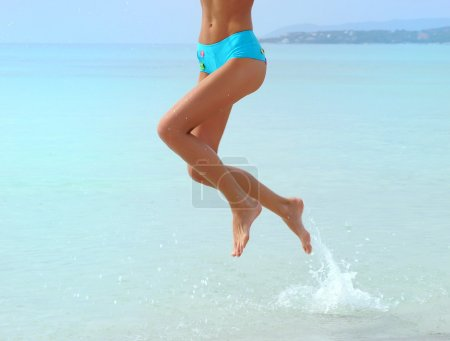 woman legs jumping  by the sea