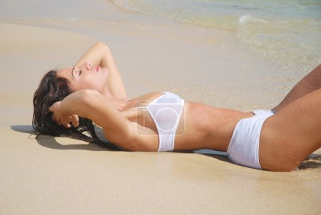 Woman perfect body sunbathing by the beach