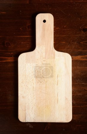 Photo for Chopping board on dark wooden table - Royalty Free Image