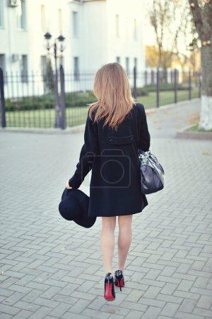 Photo pour La jeune belle fille se promène dans la rue dans un manteau et un chapeau avec un sac - image libre de droit