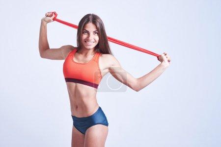 Photo pour Femme travaillant avec des groupes de fitness isolé sur blanc - image libre de droit