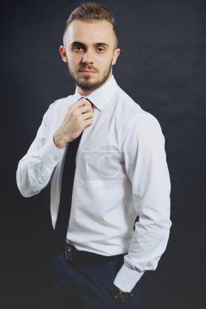Photo pour Un homme d'affaires prospère. Portrait de jeune homme confiant en tenue de cérémonie regardant la caméra et souriant tout en gardant les bras croisés et debout sur fond gris - image libre de droit