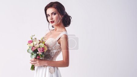 Photo for Young attractive bride with the bouquet of white roses - Royalty Free Image