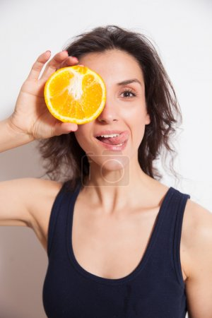 Young woman cover her eye with orange