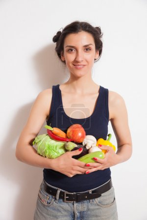 Young woman with a lot of raw fruits and vegetables
