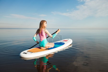 Young woman paddling on sup board