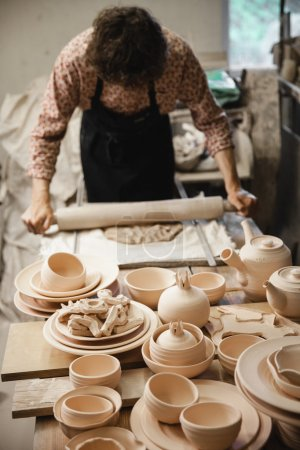 Unrecognizable potter master rolling up the clay